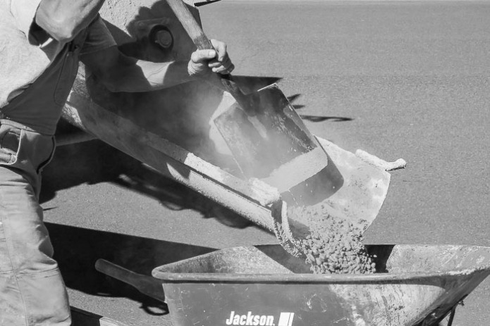 Lots of textures in this photo, concrete, shovel, wheel barrow, metal, wood.