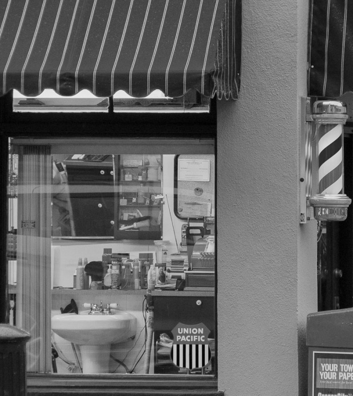 Looking into a barber shop window.
