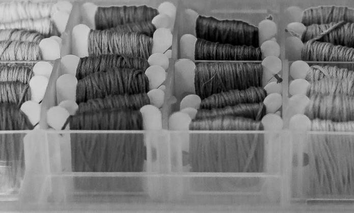 Plastic case and plastic bobbins with cross-stitch thread.