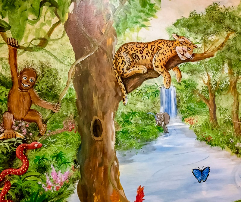 Snake crawling under a scary monkey flying through the trees on the jungle mural in one of our pediatric rooms also a butterfly flying.
